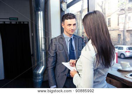 Female waiter in apron writing order for man in restaurant