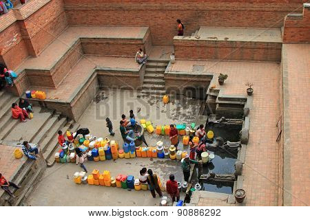 PATAN, NEPAL - APRIL 13 : People gathering at Sunken Manga Hiti - Water Conduit with carved stone Makara (mythical crocodile-elephants) waterspouts in Patan, Nepal on 13 April 2014.