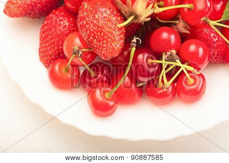 ripe juicy cherries and berry in plates on the table