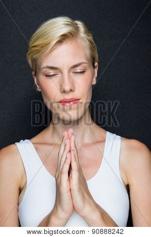 Attractive blonde woman praying on black background