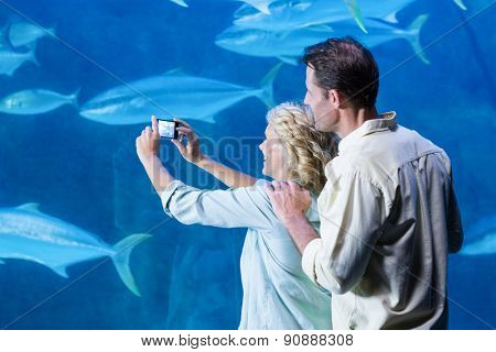 Happy couple taking a picture of fishes at the aquarium