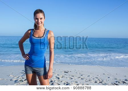 Smiling fit woman looking at camera at the beach