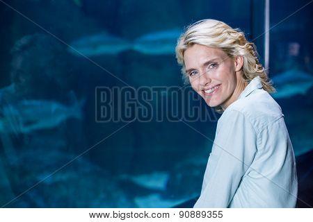 Pretty blonde looking at camera at the aquarium