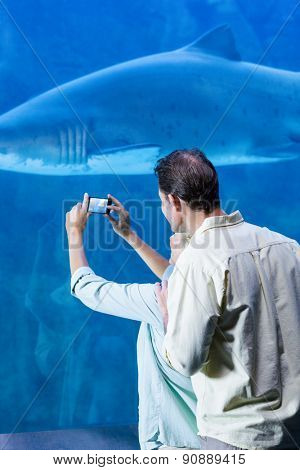 Happy couple taking a picture of a shark at the aquarium