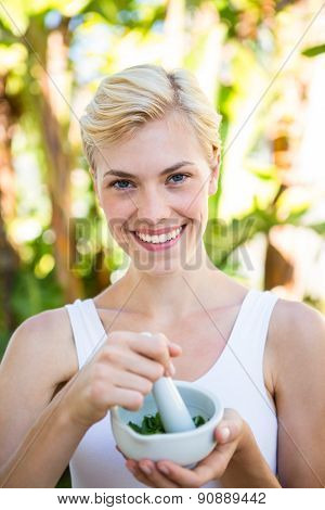 Happy blonde woman mixing herbs outside on a sunny day