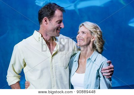 Happy couple beside the fish tank at the aquarium
