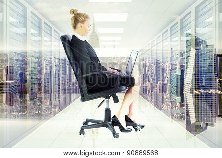 Businesswoman sitting on swivel chair with laptop against server room with towers