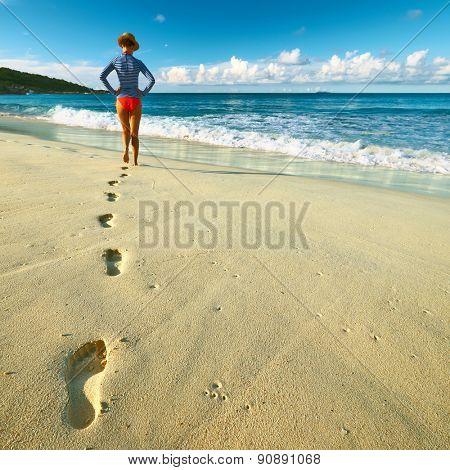 Woman at beautiful beach at Seychelles walking on sand. Focus on footprints.