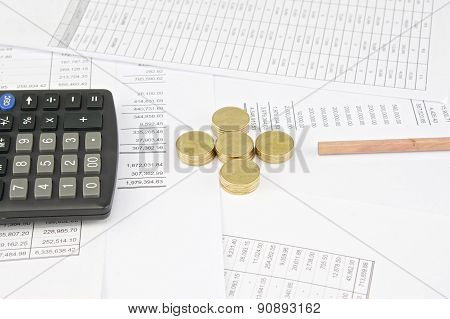 Calculator And Pencil Between Pile Of Gold Coins As Plus
