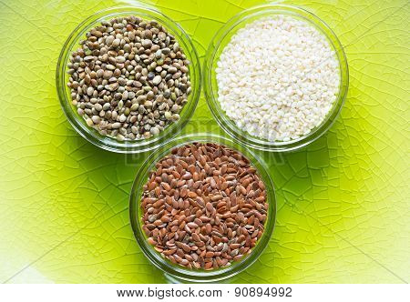 flax, sesame, and cannabis seeds in glass bowls