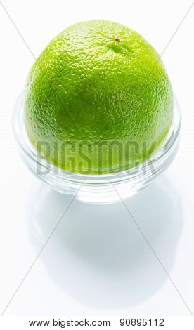 Green lime in the glass bowl isolated