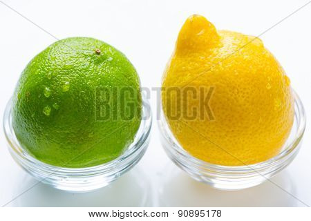 Lemon and green lime with water drops in the glass bowls isolated