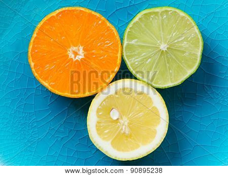 Mandarin, lemon, and green lime slices isolated on blue background