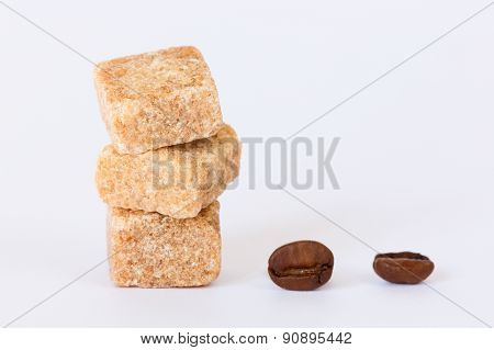 Isolated raw brown sugar cubes and coffee beans close up