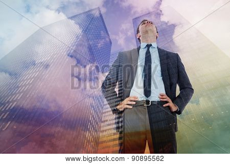 Serious businessman with hands on hips against low angle view of skyscrapers