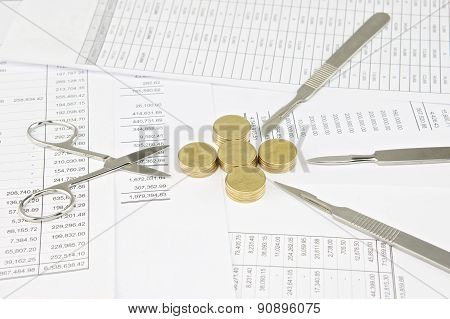 Surgical Scissors And Scalpel Between Gold Coins As Plus