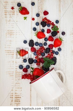 Fresh summer berries in vintage mug over wooden background,top view