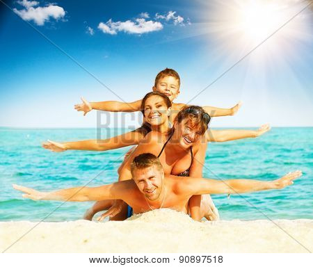 Vacation. Happy Family Having Fun at the Beach. Joyful Family. Vacation and Travel concept. Summer Holidays. Parents with Children enjoying a holiday at the sea