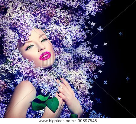 Beauty fashion model Girl with Lilac Flowers Hair Style. Beautiful Model woman with Blooming flowers on her head over black background. Nature Hairstyle. Holiday Creative Makeover. Makeup and manicure