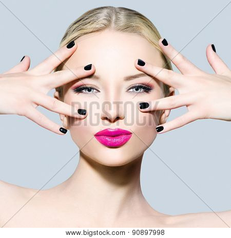 Beautiful fashion model girl with blond hair, darl manicure and bright make up. Portrait of glamour woman with makeup over grey background. Beauty female face close up with perfect make-up