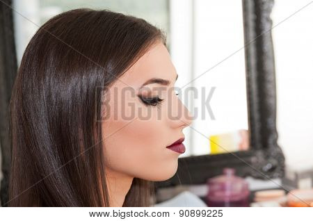 Beautiful young woman in the salon after applying makeup