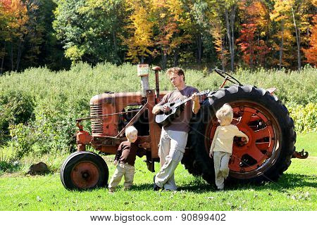 Father And Sons Playing Guitar By Old Farm Tractor