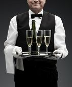 image of flute  - butler with three champagne flutes on tray - JPG