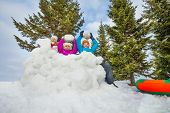 stock photo of snowball-fight  - Group of happy kids playing snowballs game together standing behind the snow wall with fir forest on the background during winter day - JPG
