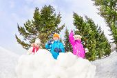pic of snowball-fight  - Girls and boy playing snowballs game together standing behind the snow wall with fir forest on the background during winter day - JPG