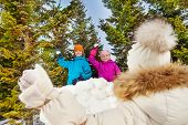 foto of snowball-fight  - View from the back of girl holding snowball while standing opposite the snow wall with boy and girl during beautiful winter day in the forest