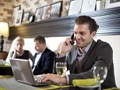 stock photo of conduction  - The young man working with the laptop uses phone - JPG