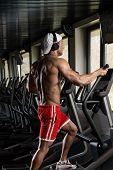pic of elliptical  - Muscular Mature Man Doing Aerobics Elliptical Walker In Modern Fitness Center - JPG