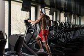 pic of elliptical  - Muscular Mature Man Doing Aerobics Elliptical Walker In Modern Fitness Center - JPG