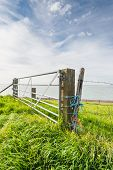stock photo of barbed wire fence  - Galvanized gate between two wooden beams and a fence with coarse meshed netting and barbed wire attached with different colored ropes - JPG