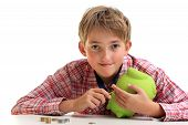 stock photo of thrift store  - The boy gets money from the piggy bank - JPG