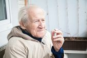 pic of muse  - thoughtful old man smoking a cigarette and musing upon a distant scene - JPG