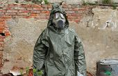 stock photo of gas mask  - Man with gas mask and green military clothes explores small plant after chemical disaster - JPG