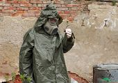 foto of gas mask  - Man with gas mask and green military clothes explores small plant after chemical disaster - JPG