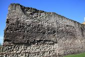 stock photo of fortified wall  - The ancient London Roman Wall with a clear blue sky - JPG