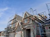 stock photo of scaffold  - Scaffolds surrounding home following application of smooth exterior stucco but prior to painting - JPG