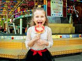 image of amusement park rides  - cute little girl with lollipop at amusement park - JPG