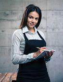 image of apron  - Happy beautiful female waiter in apron writing order - JPG