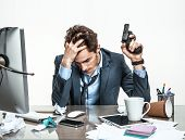 stock photo of crisis  - Manager with gun wants to commit suicide  - JPG