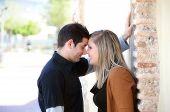 picture of flirt  - Young couple in love dressed in black and brown flirting against a brick wall in a park  - JPG