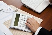 picture of anal  - Businesswoman analizing financial data with calculator in office - JPG