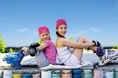 stock photo of inline skating  - Two girls in roller skates sitting side by side on the street - JPG
