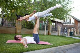 stock photo of tantra  - An attractive man and woman practice tantra yoga on a grass before the house - JPG