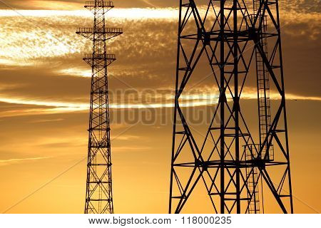 Electricity Line Towers Against Yellow Sunset Sky