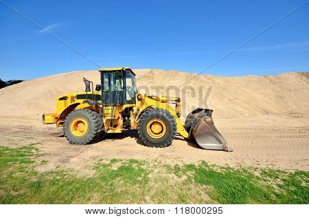 Bulldozer Working In Sand Dunes On A Clear Day