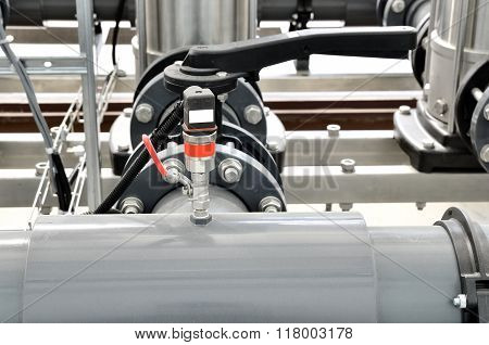 Plastic and metal pipes and other equipment in an industrial boiler room interior
